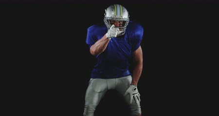 american football player : Front view of a Caucasian male American football player wearing a team uniform, pads and a helmet, clapping hands and pointing to camera, slow motion