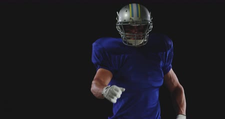 jarse : Front view close up of a Caucasian male American football player wearing a team uniform, pads and a helmet, turning around and pointing to camera, slow motion