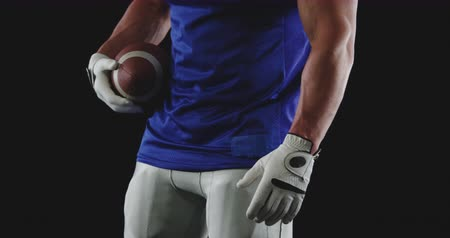 jarse : Side view mid section of a Caucasian male American football player wearing a team uniform and gloves holding a football in his hands, turning to face the front, slow motion
