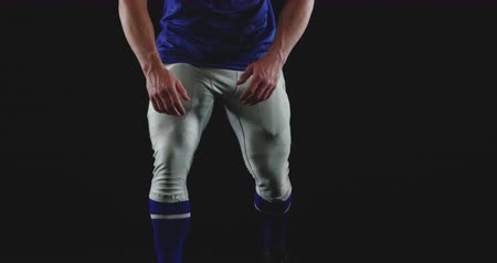 jarse : Front view close up of a Caucasian male American football player wearing a team uniform with shoulder pads and helmet, kneeling down on one leg and looking to camera, slow motion Stok Video