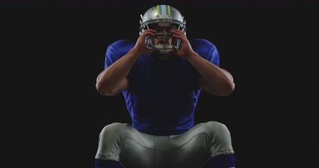 パンツ : Front view of a Caucasian male American football player wearing a team uniform, pads and holding the facemask of his helmet 動画素材