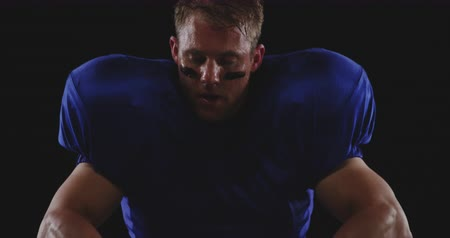 overnemen : Front view close up of a Caucasian male American football player wearing a team uniform, pads and eye black, sitting and taking off his helmet