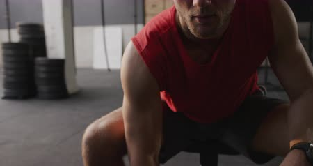 tónusú : Front view close up of an athletic Caucasian man wearing sports clothes cross training at a gym, sitting and doing curls with a dumbbell, slow motion