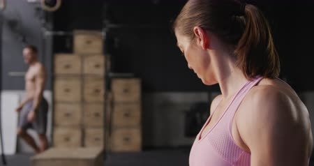 enrolar : Side view close up of an athletic Caucasian woman wearing sports clothes cross training at a gym doing curls with dumbbells, a man in the background, slow motion