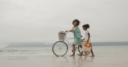 пляжная одежда : Side view of a smiling African American woman walking with her young daughter and wheeling a white bike along a beach by the sea, slow motion Стоковые видеозаписи