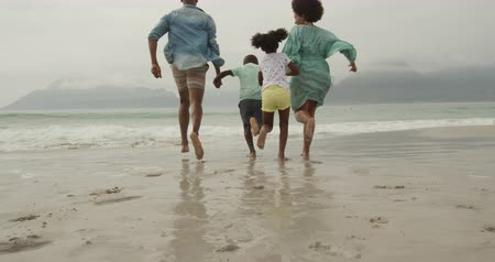 brother sister barefoot : Rear low angle view of an African American couple running on a beach towards the sea holding hands with their young son and daughter between them, slow motion