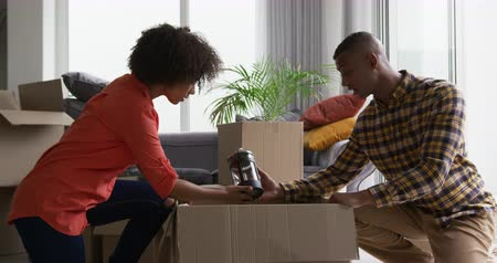 ajoelhado : Side view of an African American couple kneeling on the floor of the living room in their new home smiling and unpacking a coffee pot from a cardboard box, surrounded by packing boxes, slow motion Vídeos