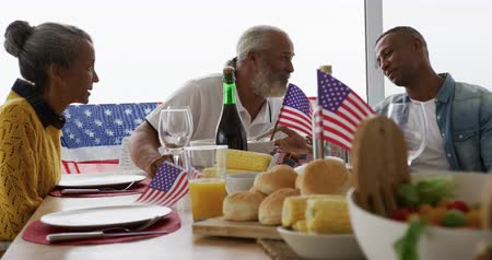 três quarto comprimento : Front view of an African American senior couple and adult son sitting at home around a dinner table decorated with US flags for an Independence Day celebration meal, talking and smiling, slow motion