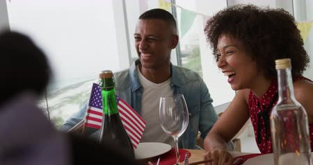 três quarto comprimento : Front view of an African American couple sitting at a dinner table decorated with US flags for an Independence Day celebration meal, laughing and smiling, slow motion Vídeos