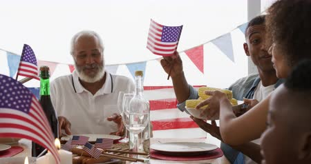 четверть : Side view of an African American multi-generation family sitting at home around a dinner table decorated with US flags for an Independence Day celebration meal, holding bowls of food, smiling and waving flags, slow motion