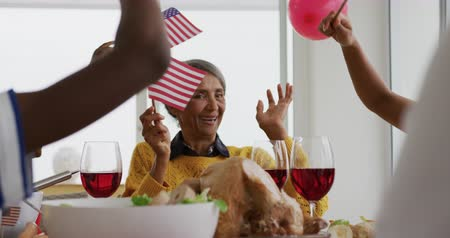 três quarto comprimento : Front view of a senior African American grandmother sitting at a dinner table decorated with US flags for an Independence Day celebration meal with her family, waving flags and playing with balloons, slow motion Vídeos