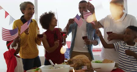 jídelna : Front view of an African American multi-generation family standing at home around a dinner table for an Independence Day celebration meal, waving flags, the adults holding glasses of wine, with a sparkler glowing in the foreground, slow motion