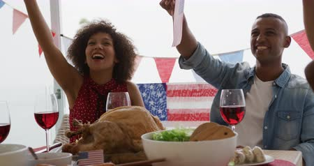 três quarto comprimento : Front view close up of an African American multi-generation family sitting at home around a dinner table decorated with US flags for an Independence Day celebration meal, having fun waving flags and playing with balloons, slow motion