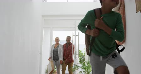 front door : Front view low angle of an African American couple and their young mixed race son arriving home, the son running in carrying a rucksack as they walk behind smiling in the sunlit corridor, slow motion