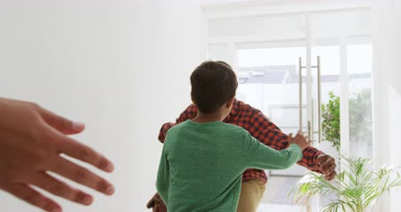 front door : Rear view of a mother and her young mixed race son greeting his African American father as he arrives home, the son running to greet him in the sunlit corridor, slow motion