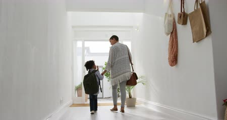 front door : Rear view low angle of a young African American girl and her mother leaving home, talking and holding hands as they walk in the sunlit corridor towards the front door, slow motion