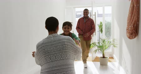 arriving : Rear view of an African American woman greeting her young mixed race son arriving home with his dad, the son running in carrying a rucksack with his dad walking behind smiling in the sunlit corridor, slow motion