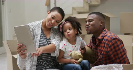 picture box : Front view of an African American couple and their young daughter in the hallway of their new home, taking a break from unpacking boxes, sitting on the floor using a tablet computer to take a selfie together, slow motion Stock Footage