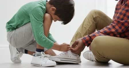 ajoelhado : Side view close up of an African American man sitting on the floor while his mixed race young son kneels down tying his shoelace for him, slow motion Stock Footage