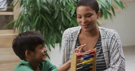 trabalhos domésticos : Front view close up of an African American woman and her mixed race young son at home in the kitchen sitting at a table, using an abacus together and smiling, slow motion