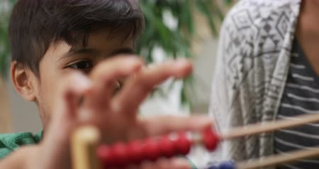 abacus : Close up of a mixed race young boy at home sitting at a table and counting with an abacus, selective focus, slow motion