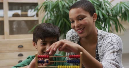 abacus : Front view close up of an African American woman and her mixed race young son at home in the kitchen sitting at a table, using an abacus together and smiling, slow motion