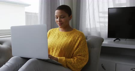 reclináveis : Front view of an African American woman at home in the living room, sitting on a sofa with her legs up using a laptop computer and smiling, slow motion Vídeos
