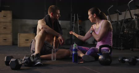 cross training : Front view of an athletic Caucaian woman and man sitting on the floor at a gym taking a break from their cross training and discussing exercises, slow motion Stock Footage