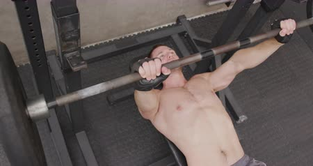 músculos : High angle view of a shirtless athletic Caucasian man cross training at a gym lying on a bench lifting weights on a barbell, slow motion