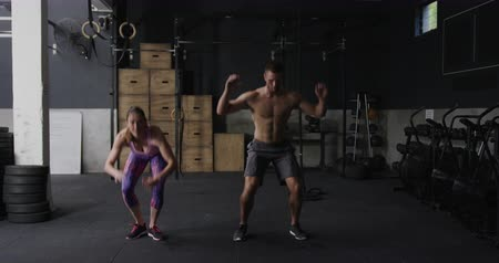 squat : Front view of an athletic Caucasian woman wearing sports clothes and a shirtless Caucasian man cross training at a gym doing burpees, slow motion