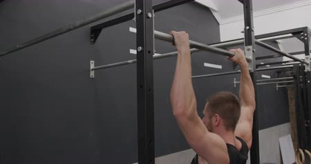 pull out : Side view of an athletic Caucasian man wearing sports clothes cross training at a gym doing chin ups on a bar, slow motion Stock Footage