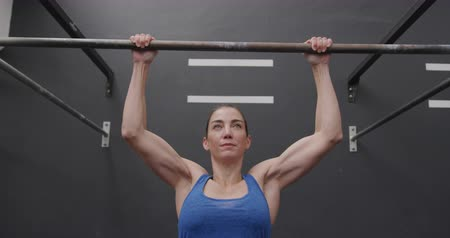 pull out : Front view close up of an athletic Caucasian woman wearing sports clothes cross training at a gym doing chin ups on a bar, slow motion