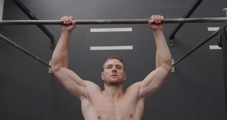 pull out : Front view close up of a shirtless athletic Caucasian man cross training at a gym doing chin ups on a bar, slow motion
