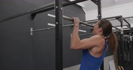cross training : Side view of an athletic Caucasian woman wearing sports clothes cross training at a gym doing chin ups on a bar, slow motion Stock Footage