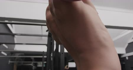 contra : Side view close up of a shirtless athletic Caucasian man cross training at a gym doing chin ups on a bar, slow motion