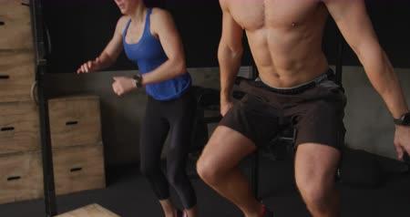 flexibilidade : Front view of a shirtless muscular Caucasian man and an athletic Caucasian woman wearing sports clothes cross training at a gym, jumping off and back on to boxes, slow motion Stock Footage