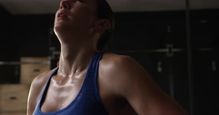 perspiring : Front view close up of an athletic Caucasian woman wearing sports clothes cross training at a gym catching her breath after intensive exercising, slow motion Stock Footage