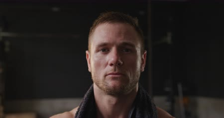perspiring : Portrait close up of a shirtless athletic Caucasian man cross training at a gym, taking a break from exercise with with a towel around his neck looking to camera after an intensive work out, slow motion Stock Footage