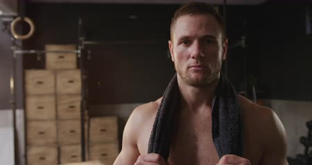 perspiring : Portrait of a shirtless athletic Caucasian man cross training at a gym, taking a break from exercise, holding a towel around his neck looking to camera after an intensive work out, slow motion