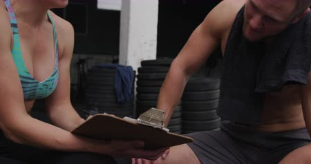 señalando : Front view close up of a shirtless athletic Caucasian man cross training at a gym taking a break, sitting with a towel around his neck and talking with a Caucasian female trainer holding a clipboard, slow motion