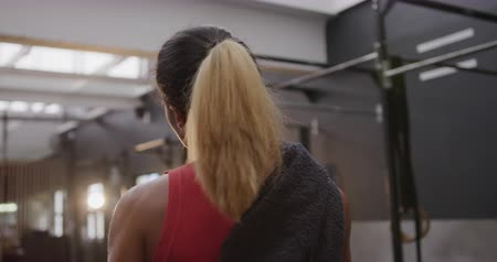cross training : Rear view close up of an athletic mixed race woman wearing sports clothes cross training at a gym walking in the gym holding a towel Stock Footage