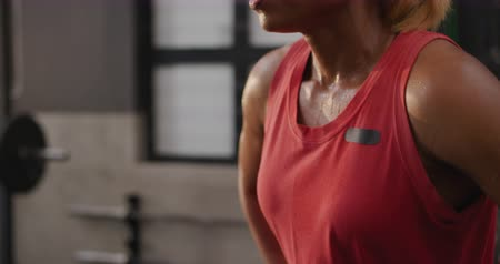 perspiring : Side view close up of an athletic mixed race woman wearing sports clothes cross training at a gym stading with hands on hips recovering after an intensive workout, slow motion