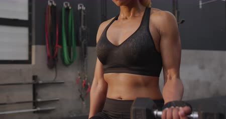 undefined : Front view close up of an athletic mixed race woman wearing sports clothes cross training at a gym sitting doing bicep curls lifting dumbbells, slow motion Stock Footage