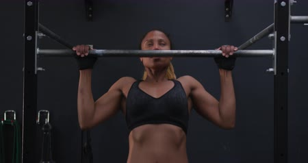 contra : Front view of an athletic mixed race woman wearing sports clothes cross training at a gym Side view of an athletic mixed race woman wearing sports clothes cross training at a gym doing pull ups on a bar, slow motion