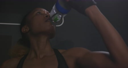 flexibilidade : Front view rack focus close up of an athletic mixed race woman wearing sports clothes cross training at a gym taking a break, standing and drinking from a bottle, slow motion