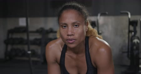 perspiring : Portrait close up of an athletic mixed race woman cross training at a gym, taking a break between exercises and looking straight to camera, slow motion