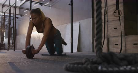 ajoelhado : Front view of an athletic mixed race woman wearing sports clothes cross training at a gym doing exercises on the floor using an ab wheel, slow motion