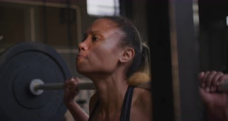 squatting : Side view close up of an athletic mixed race woman wearing sports clothes cross training at a gym squatting and lifiting weights with a barbell on her shoulders, slow motion Stock Footage