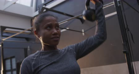 chaleira : Front view close up of an athletic mixed race woman wearing sports clothes cross training at a gym, lifting a kettlebell weight over her head, slow motion Vídeos