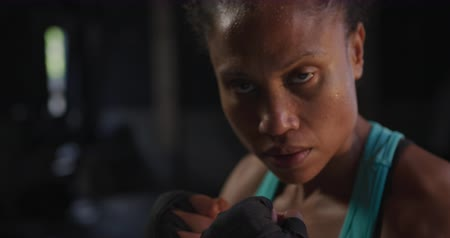 undefined : Portrait close up of an athletic mixed race woman cross training at a gym, holding a guard position with wrapped hands while boxing training Stock Footage